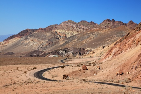 Winding road in Death Valley. Dry clay soil and a cloudless sky photo