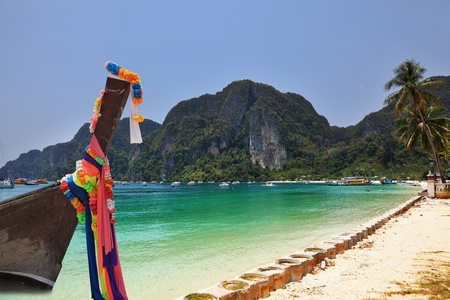 The native boat decorated with silk tapes is moored in thin gentle beach sand. Island Phi-Phi, Thailand  photo
