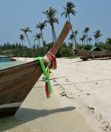 Boat Longtail decorated with silk tapes expects tourists. Island Phi-Phi, Thailand photo