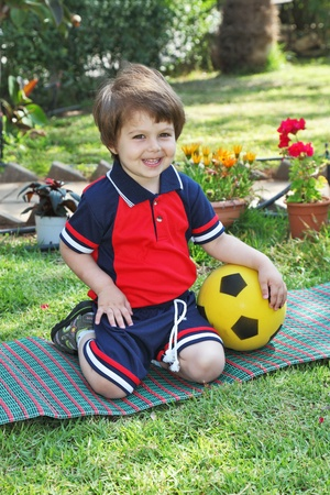 A little boy with a charming smile, poses on a green lawn. He carried a yellow ball Stock Photo - 10922528