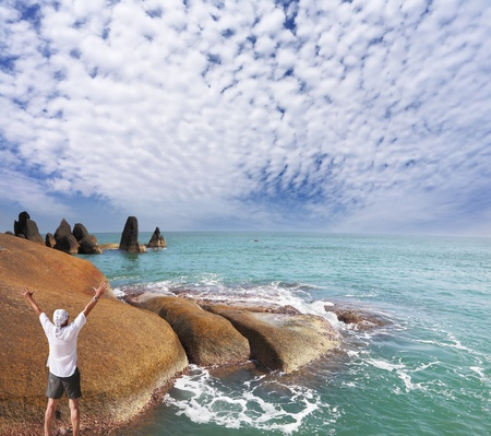 A lone tourist happily welcomed the new day on the rocky seashore Stock Photo - 10922526