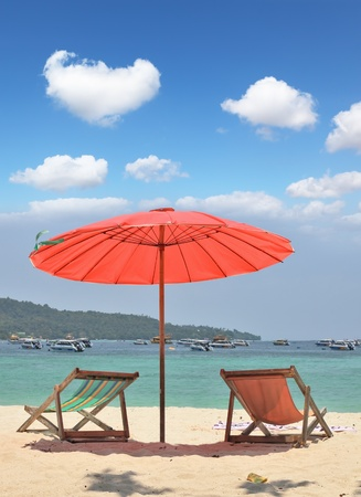 Tropical paradise on the bank of the azure sea. A red beach umbrella and chaise lounges on white sand