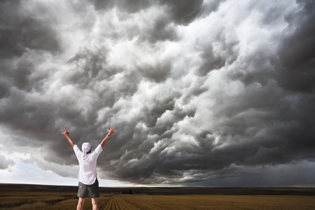 The enthusiastic tourist welcomes thunderstorm above Montana. Fields after a harvest photo