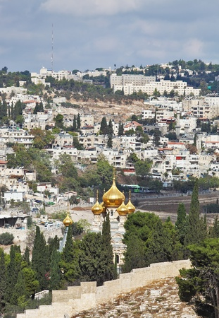 Magnificent gold domes of orthodox church in Jerusalem. Jerusalem on hills and the cloudy sky  photo