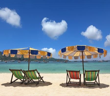 Beach paradise on the Krabi, Thailand. Colorful parasols and deck chairs are waiting for convenient travel Stock Photo