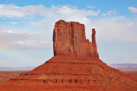 The famous Mittens in Monument Valley. The cliffs of red sandstone on the background of the cloudy sky photo