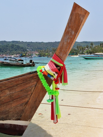 expects: Boat Longtail decorated with silk tapes expects tourists. Island Phi-Phi, Thailand