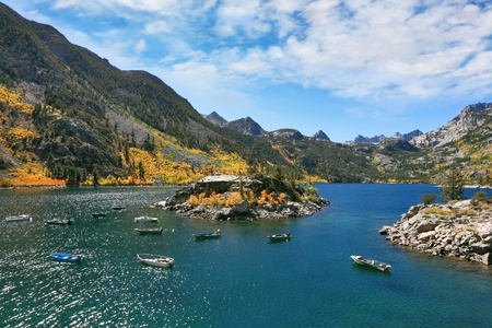 Fishing paradise. Azure lake in autumn mountains. Fishing boats turn round small picturesque island photo