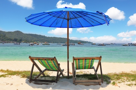 A picturesque dark blue beach umbrella and striped chaise lounges on white beach sand  photo