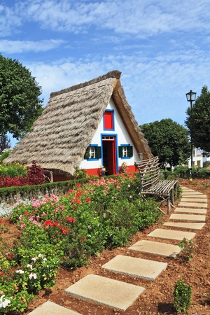 Madeira Island, the city Santana. Cosy chalet with a triangular thatched roof. Before the house - garden with beautiful flower beds.  Редакционное