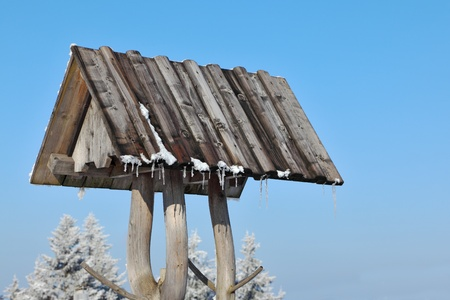 tatras: A bright sunny winter morning in the Tatras. Roof of a rural well with icicles