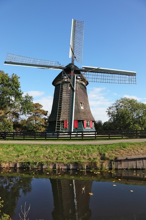 The ancient windmill is reflected in water of a small pond. Clear autumn day in the Netherlands photo