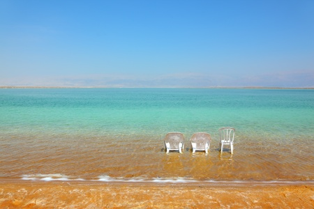 White beach armchairs and a chair in the warm clear water beach. Beach at the Dead Sea in May photo
