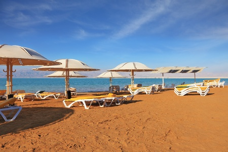 A magnificent beach with clean yellow sand on the shore of the Dead Sea. Guests of the hotel - beach umbrellas and beach loungers photo
