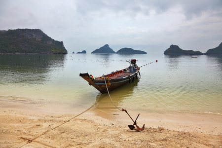 Thai Longtail boat moored on a sandy beach with an anchor. Picturesque bay on the island surrounded by islands  photo