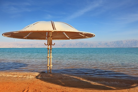 A magnificent beach with clean yellow sand on the shore of the Dead Sea  Guests of the hotel - beach umbrellas  photo