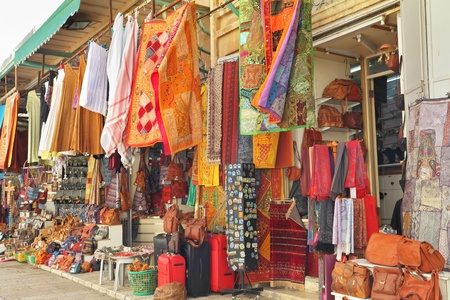 souvenir traditional: Variegated colors of oriental bazaar. The Arabian market in Jerusalem - bright motley fabrics and clothes are hung out for sale