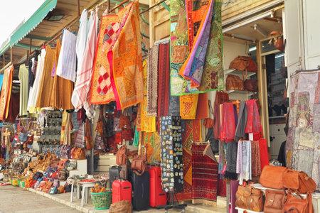 Variegati colori di bazar orientale. Il mercato arabo di Gerusalemme - luminosi tessuti multicolori e vestiti sono appesi fuori per la vendita