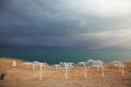 Winter on the Dead Sea  Empty beach umbrellas, green water and purple thunderheads Stock Photo - 13409527