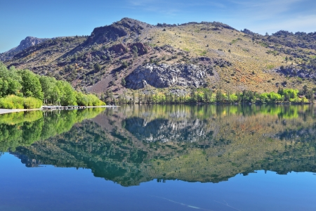 reflects: A lovely shallow lake in the mountains of California. In the smooth water surface reflects the majestic mountains and pine forests