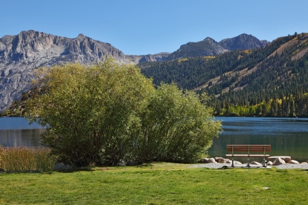 Charming lake in California. Green, grassy lawn and a cozy bench photo