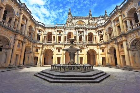 Beautifully preserved castle - palace of the Templars  Courtyard surrounded by galleries  In the center - a fountain with a pool in the shape of a cross  Portugal, Tomar