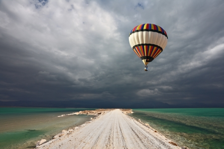 Picturesque bright balloon with a basket of passenger flying in a thunderstorm over the shoal Dead Sea