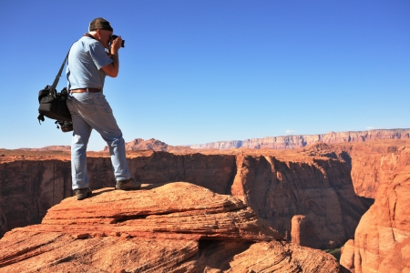 Professional photographer photographed on a steep and high bank of the river  The famous Colorado River in the picturesque Horseshoe bend   photo