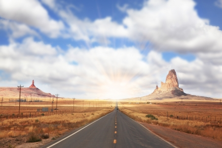Gorgeous American Highway. Monument Valley in Utah on a cloudy wind. Shining rays of evening sun sharp light the way photo