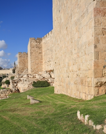 defensive: Defensive wall of the ancient holy Jerusalem, lit by the bright sun. Wonderful green lawn
