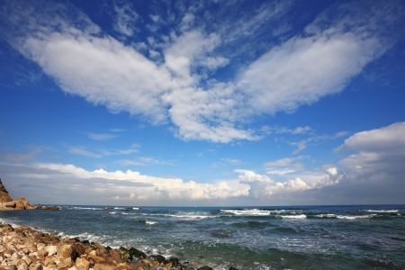 The Mediterranean coast. Azure waves and spectacular flying clouds Stock Photo - 15794815