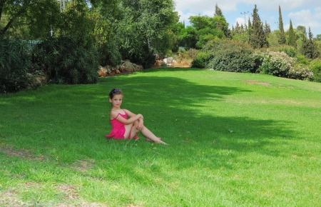 Lovely girl in pink sarafan poses on a green grassy lawn Stock Photo