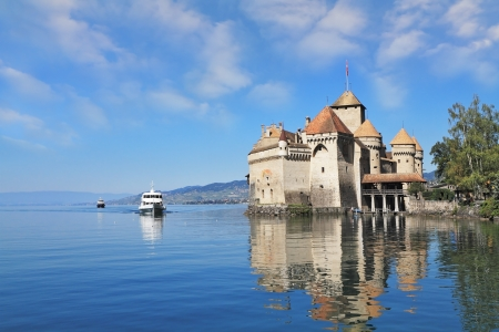 The white tourist motor ship floats by a magnificent medieval castle  World-wide well-known Ch&Atilde,&cent,teau de Chillon on Lake Geneva