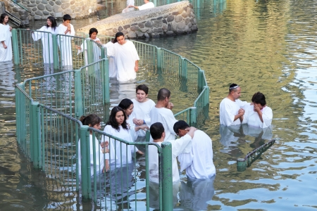 Yardenit, Israel - January 21: Christian pilgrims ritual baptism in the waters of the Jordan River in the days of the Feast of Holy Baptism 21 January 2012 at Pilgrim baptismal site Yardenit, Israel. Pilgrims enter the water, dressed in special white chri Редакционное