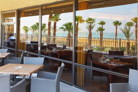 Mirror showcase expensive hotel reflects the sea, beach, palm trees and restaurant tables Stock Photo - 17175738