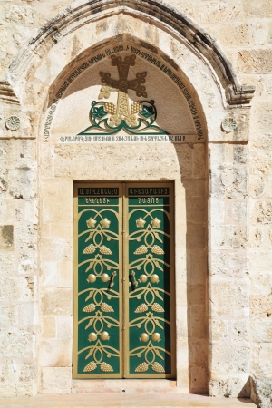 Entrance to the Coptic Church of the Holy Sepulchre in Ierusalime.Green doors are decorated by gold grape clusters and pomegranates photo