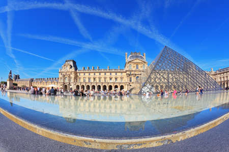 Paris, September 8  The world-famous entrance to the Louvre - the glass pyramid and a fountain September 8, 2012 in Paris  Tourists resting on a granite fence fountain  Traces in the sky jet  Picture taken Fisheye lens