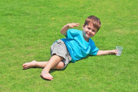 The charming four-year-old boy with pleasure has a rest on a green grassy lawn Stock fotó