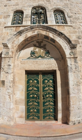 The side entrance to the Temple of the Holy Sepulcher lit bright sun. Picturesque green door decorated with gold ornaments. Above the door of the golden cross and three semicircular windows Stock Photo - 17333287