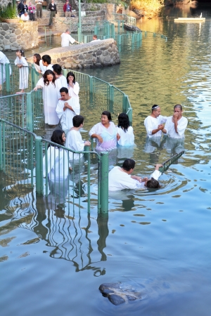 baptize: Yardenit, Israel -  The ritual baptism of Christian pilgrims in the sacred waters of the Jordan River in the days of the Feast of Holy Baptism  at Pilgrim baptismal site Yardenit, Israel. Pilgrims enter the water, dressed in special white christening shir Editorial