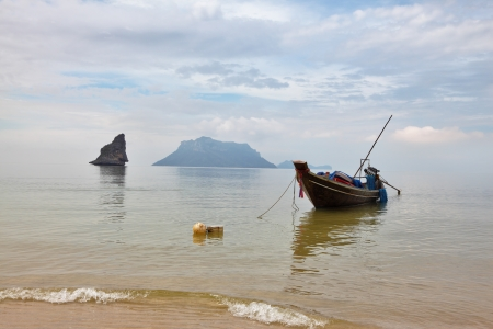 Thai Longtal boat moored on a sandy beach with an anchor. Picturesque bay on the island surrounded by islands  photo