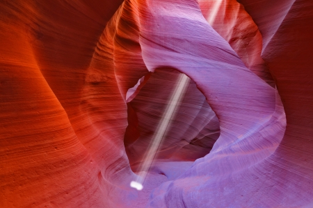 arizona: Noon in a red-orange Antelope Canyon. A thin ray of sunlight illuminates the sandy bottom of the canyon