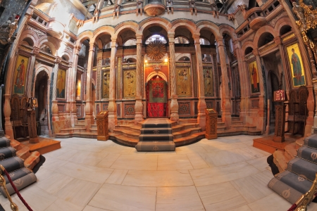 The huge marble hall in the Holy Sepulchre lit bright sun. On the walls of the hall paintings on biblical themes. Entry to the altar of the draped red curtain Stock Photo - 17586189