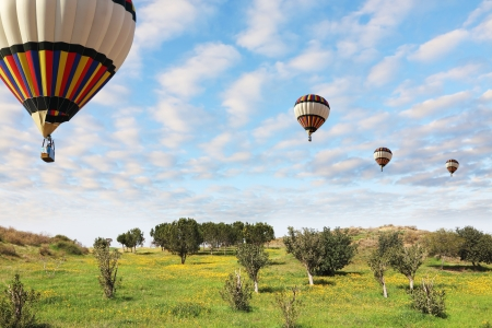 Four large bright balloons with a passenger basket fly by over spring blossoming fields photo