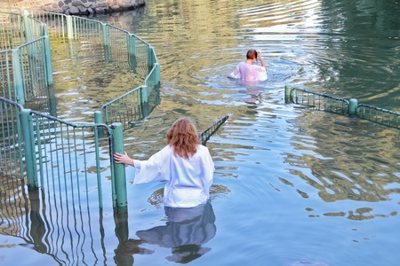 Yardenit, Israel - January 21  Baptism of Christian pilgrims in the holy waters of the Jordan River in the days of the Feast of Holy Baptism 21 January 2012 at Pilgrim baptismal site Yardenit, Israel  Pilgrims enter the water, dressed in special white chr Editorial