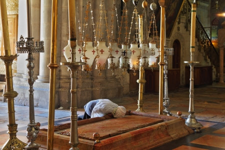 The pilgrim in white clothes passionately prays under icon lamps   Temple of the Holy Sepulcher in Jerusalem  The oldest Christian sanctuary - Stone of Unction   photo