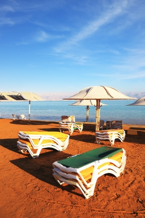 Beautiful sunny day at a beach resort. The Dead Sea, the green beach chairs and umbrellas waiting for tourists photo