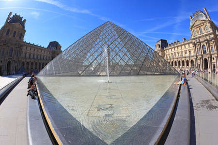 Paris, September 8: The world-famous entrance to the Louvre - the glass pyramid and a spectacular fountain of September 8, 2012 in Paris.