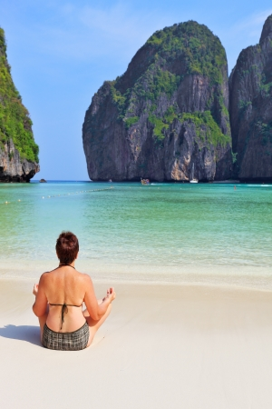 Trim elderly woman hatha yoga on the beach. Maya Bay Island in the Andaman Sea, Thailand photo