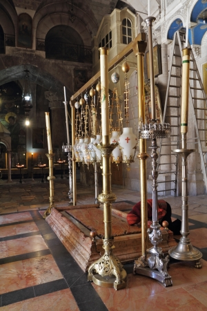 passionately:  The pilgrim in red clothes passionately prays under icon lamps  Temple of the Holy Sepulcher in Jerusalem  The oldest Christian sanctuary - Stone of Unction